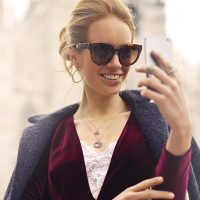 woman-in-maroon-long-sleeved-top-holding-smartphone-with-972884-1200x628